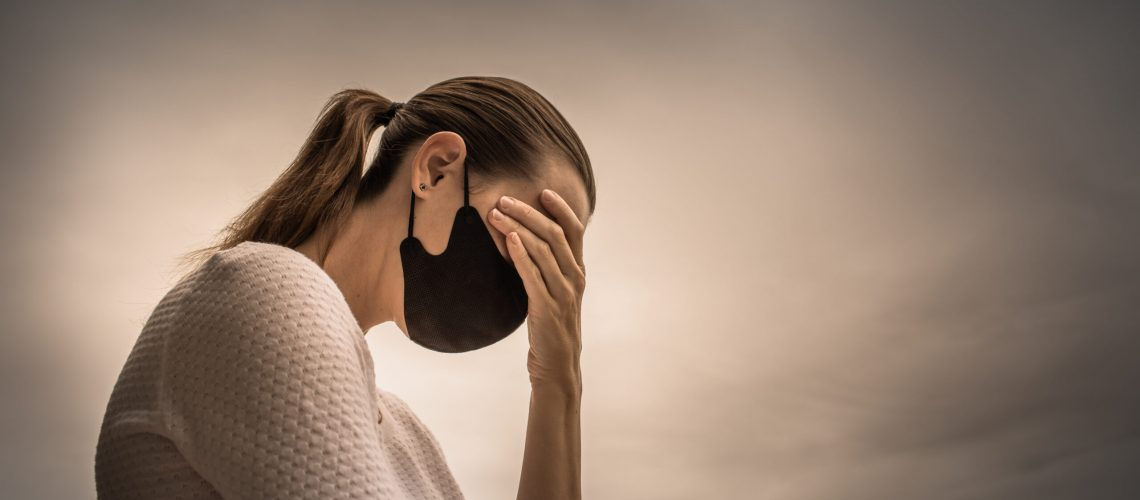 Stressed female wearing protective face mask. Coronavirus, fear, health concept.